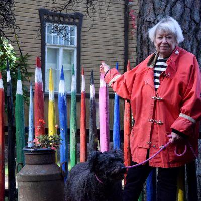 Maikki Harjanne och hennes hund vid staket av stora pennor.