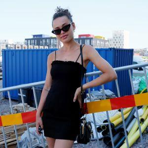 Kiara Nelson ute på byggarbetsplats i somrig klänning.