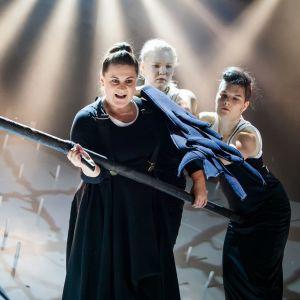ur kalevalaproduktionen på ÅST: en kvinna håller i en lie och har två kivnnor bakom sig