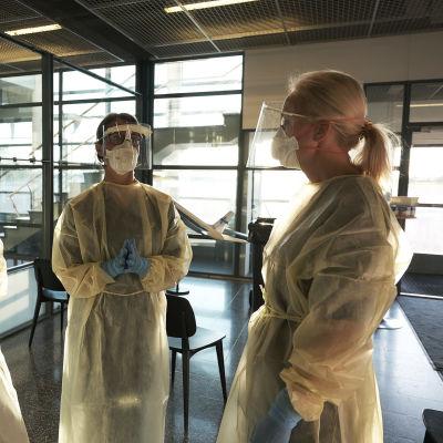 Tre kvinnor i skyddsdräkt står och väntar på att coronatesta resenärer vid flygplatsen i Åbo.