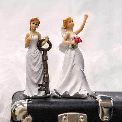 Tårtdekoration bestående av ett par kvinnor iklädda brudklänningar som står ovanpå en portfölj. Den ena har en nyckel i handen och den andra en blombukett.