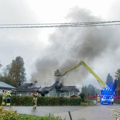 Pelastuslaitoksen nostokoriauto kurottuneena voimakkaasti savuavan omakotitalon ylle, kuvassa näkyy myös pelastushenkilöstöä.