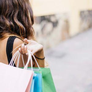 En kvinna med shoppingkassar i handen.