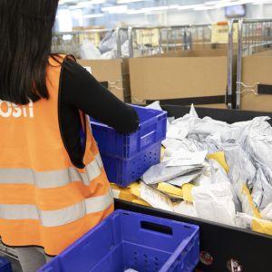 nainen lajittelee paketteja