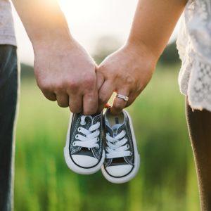 Vanhemmat pitävät toisiaan kädestä, käsissä vauvan tennarit