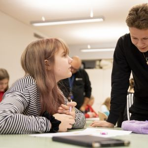 Niklas Ansamaa juttelee koulussa oppilaan kanssa.