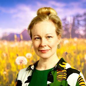 Aja Lund ser rakt in i kameran med ett litet leende med en sommaräng i bakgrunden.