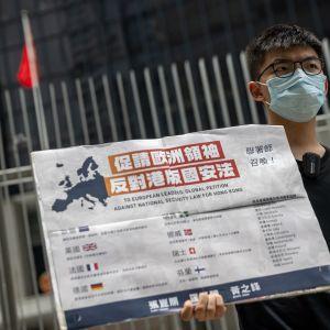 Joshua Wong pitää kädessään kiinankielistä plakaattia