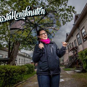 Kvinna med brunt hår, rosa scarf och utejacka står utanför flera trähus med ett paraply i handen.
