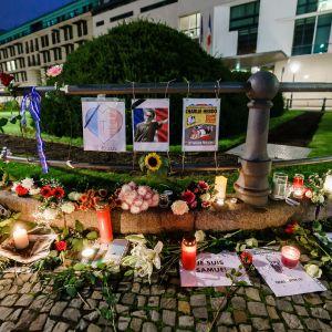 Kukkia, kynttilöitä ja kuvia kadulle perustetulla muistopaikalla.