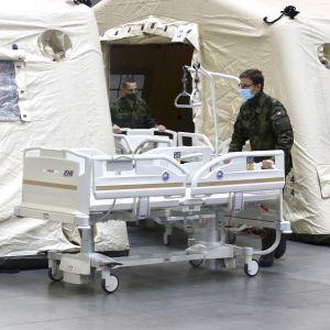 Sotilaat siirtävät sairaalasänkyä telttamaiseen rakennukseen.