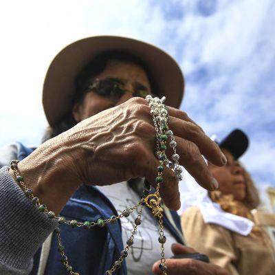Paljon ihmisiä tuli katsomaan Paavia puistoon Ecuadorin Quitossa. Kuvassa olevassa naisella on koruriipuksia kädessään.