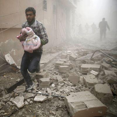 Mies kantoi vauvaa pommi-iskussa tuhoutuneiden talojen keskellä Douman kaupungissa, Syyriassa sunnuntaina.