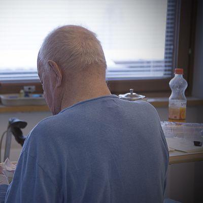 Potilas istuu sairaalavuoteella.