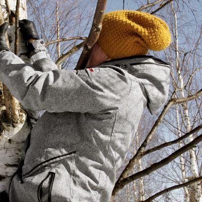 Nainen riustaa lnnunpönttöä puuhun.