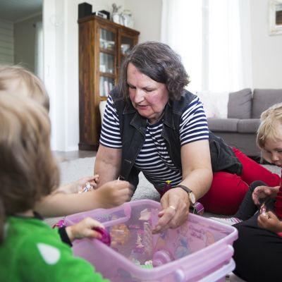 Kodinhoitaja leikkii pikkulasten kanssa.