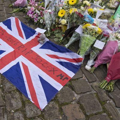 Yhdistyneen kuningaskunnan lippu, jonka päälle on kirjoitettu mustalla tussilla: 1974-2016 RIP JO COX MP. Lipun vieressä on paljon kukkakimppuja.