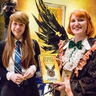Kaksi naista joista toinen pitelee Harry Potter -kirjaa käsissään.