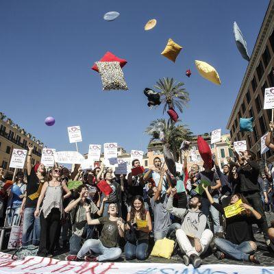 Mielenosoittajat heittelevät tyynyjä ja kondomeja ilmaan.