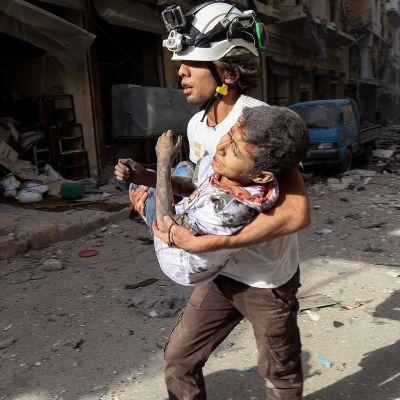 Avustustyöntekijä kantaa loukkaantunutta lasta Aleppossa.