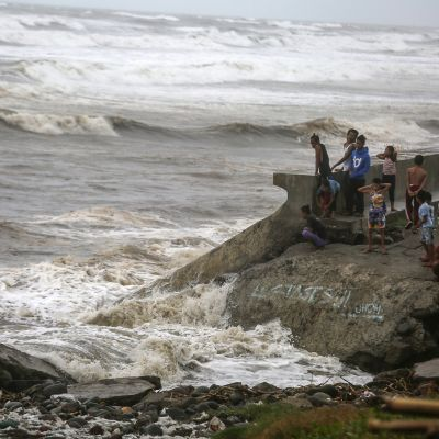 Filippiiniläisiä katsomassa myrskyävää merta.