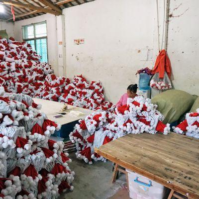 Nainen kokoaa lakkeja Yiwun pukinlakkitehtaassa.