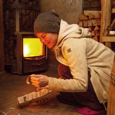Saara Lehtonen lämmittää saunaa.