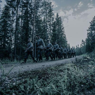 Sotilaat marssivat metsätiellä
