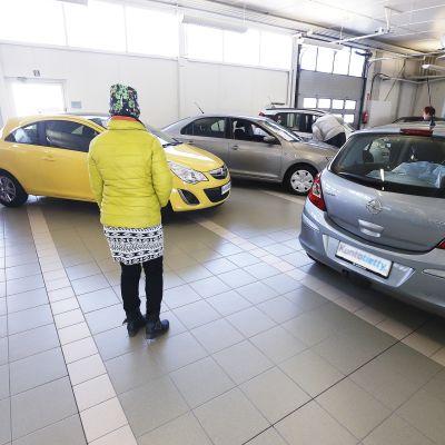 Ihmisiä autokaupassa.