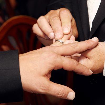 Mies pujottaa sormuksen miehensä sormeen