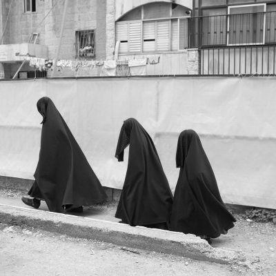 Kolme henkilöä kävelemässä koko vartalon peittävässä mustassa asussa.