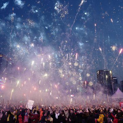Eteläkorealaiset räjäyttelevät ilotulitteita.