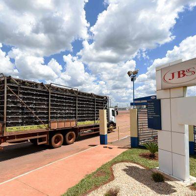 Rekka ajaa brasilialaisen JBS-lihatuottajan portista sisään. Rekan lava on täytetty häkeillä, joissa on kananpoikia.