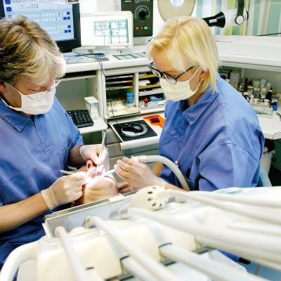 Hammaslääkäri ja hammashoitaja hoitavat potilaan hampaita.