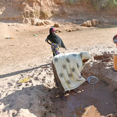 Kaksi naista ja tyttö keräämässä vettä pienestä ja kuivasta hiekkakuopasta.