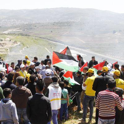 Palestiinalaiset osoittAvat mieltään Qaryotin kylän luona.