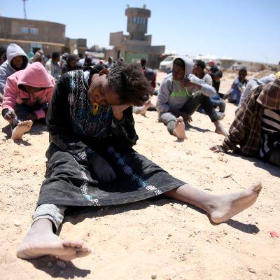 ihmisiä istuu hiekkarannalla