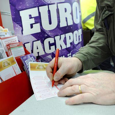 Mies täyttää Eurojackpot-kuponkia.