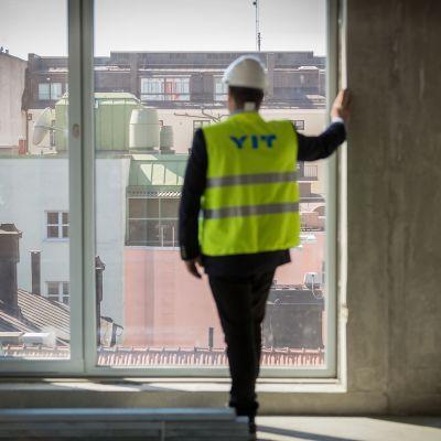 Mies katselee ikkunasta ulos maisemaa.