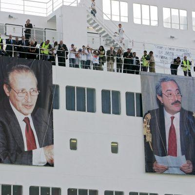 Laivan sivussa on suurikokoiset tuomarien kuvat. Kannella ihmisiä.