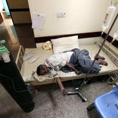 Mies makaa hoitovuoteella tipassa.