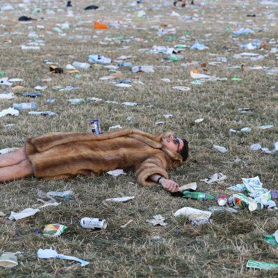 Mies makaa roskien peittämän Glastonburyn festivaalialueen nurmikolla festivaalin päätyttyä.