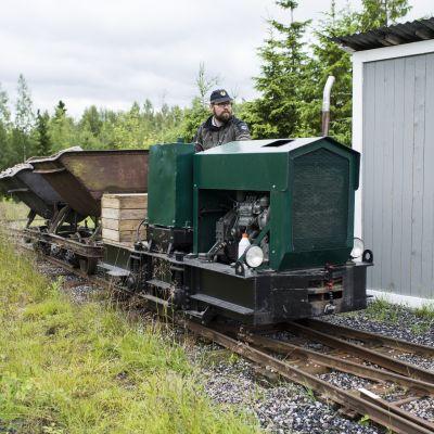 Mies ajaa kotipihallaan olevalla rautatiellä.