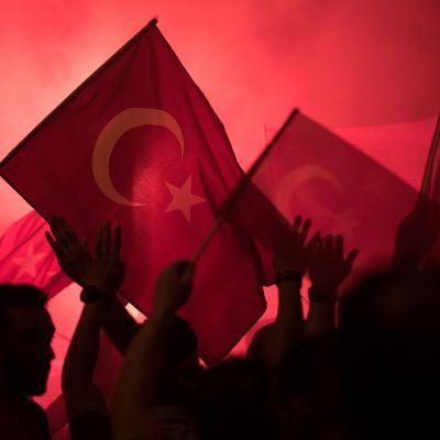 Turkin lippuja, taustalla punaista savua