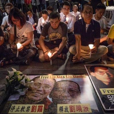 Ihmisiä istuu kynttilöiden kanssa, etualalla Liu Xiaobon ja hänen puolisonsa Liu Xian kuvat.