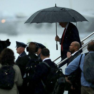 Presidentti Donald Trump astuu alas lentokoneesta sateenvarjon alla. Ympärillä on lehdistöä ja turvamiehiä.