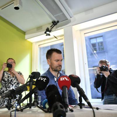 Gustafsson mikrofoneja edessään, kuvaajia ympärillään.