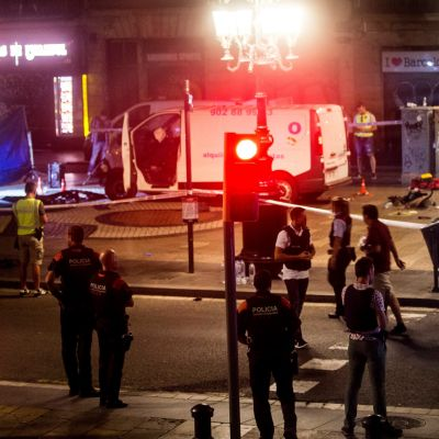 Valkoinen pakettiauto kadulla. Poliisit ohjaavat ihmisiä.