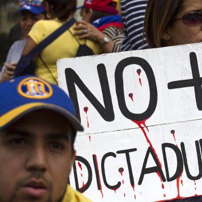 Lähikuva mielenosoittajista, joiden kyltissä lukee Ei diktatuurille