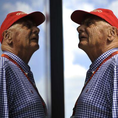 Niki Lauda katselee yläviistoon, peilikuva hänestä heijastuu kuvassa vasemmalla.